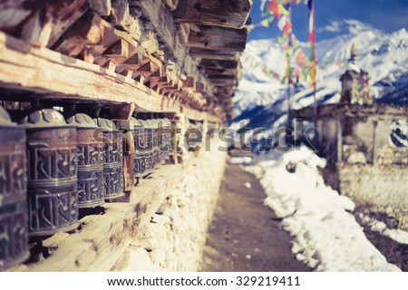 Prayer wheels in high Himalaya Mountains, Nepal village. Annapurna Two range region in Nepal, located at Annapurna Circuit Trekking Hiking Trail - stock photo