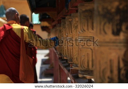 Prayer wheels with young monks passing by.