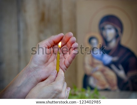 Prayer with a candle - stock photo