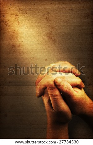 Prayers hands and sunbeam on old nostalgic background - stock photo