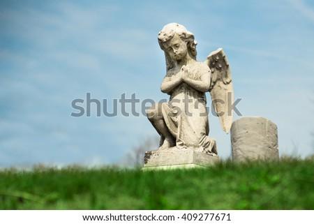 Praying Angel statue in graveyard - stock photo