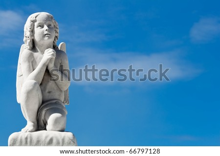 Praying angel with a blue sky background - stock photo