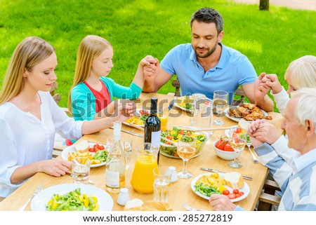 Praying before dinner. Top view of family of five people holding hands and praying before dinner while sitting at the table outdoors  - stock photo