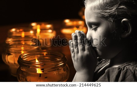 Praying child with candles on background. MANY OTHER PHOTOS FROM THIS SERIES IN MY PORTFOLIO.  - stock photo