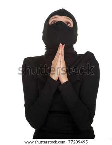 praying female thief in black clothes and balaclava - stock photo