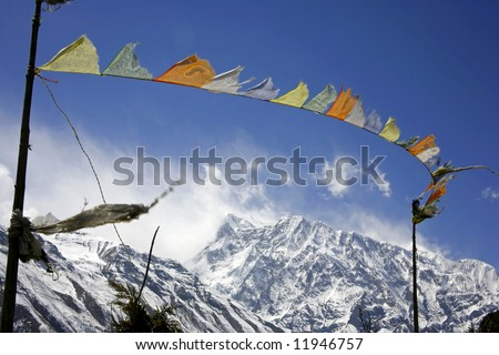 praying flags floating in the wind in front of the annapurnas, nepal - stock photo