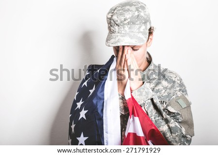 Praying for lost comrades. US Soldier in grief.  - stock photo