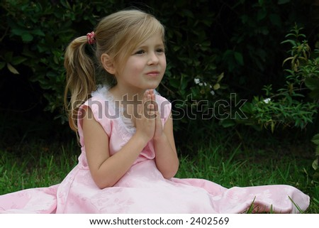 praying girl on the grass - stock photo