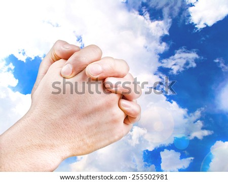 Praying Hands against the sky - stock photo