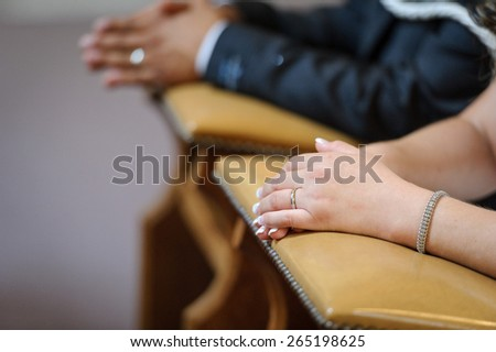 Praying hands of bride and groom - stock photo