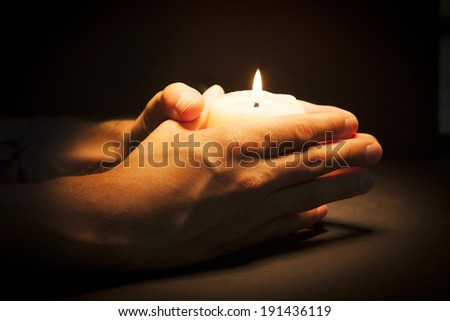 Praying Hands with candle in black background - stock photo