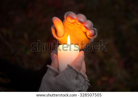 Praying Hands with candle in dark background - stock photo