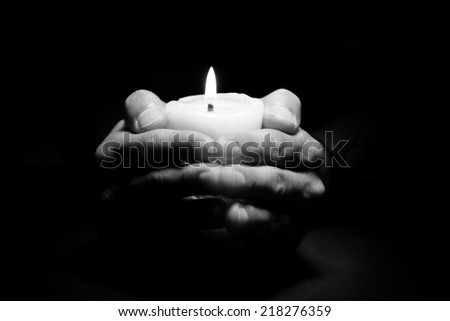 Praying Hands with candle in dark background black and white - stock photo
