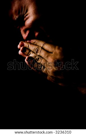 Praying in darkness concept. Pain, anger and grief face expressions - stock photo
