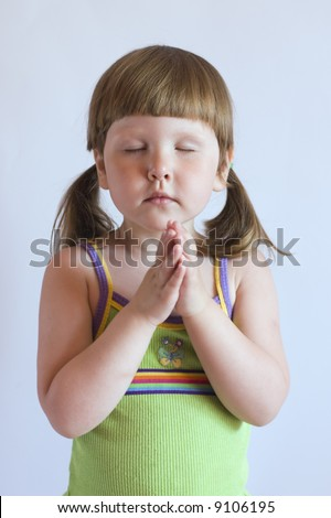Praying little girl in green top with ponytails, studio - stock photo