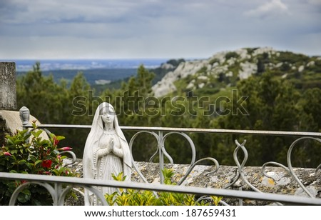 Praying Madonna statue with a rosary behind  the metal grave fence at the cemetery in Les Baux-de-Provence (Provence, France) and a beautiful landscape at backgrounds. - stock photo