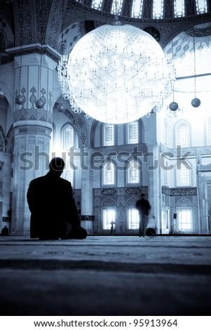 Praying Muslim man  silhouette in Kocatepe Mosque - Ankara, Turkey - Split toned - stock photo