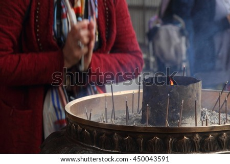 Praying near burning incenses in a buddhist temple - stock photo