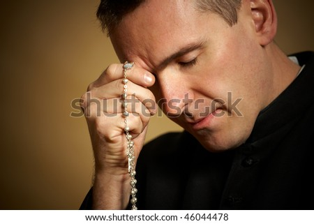 Praying priest with rosary in his hands - stock photo