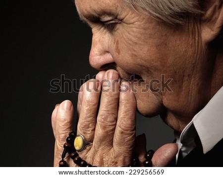 Praying senior woman. - stock photo