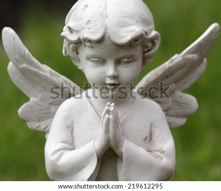 praying sweet angel figurine isolated on green background - stock photo