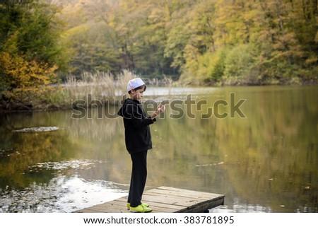 praying teenager standing by the lake - stock photo