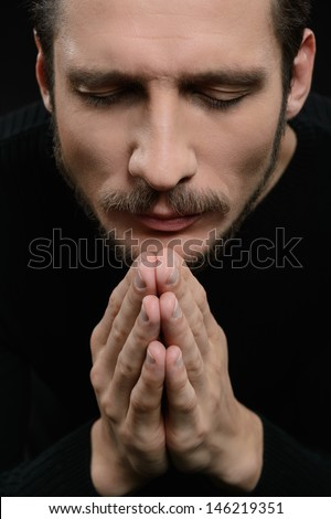 Praying with eyes closed. Devout bearded man praying and holding his hands clasped while isolated on black