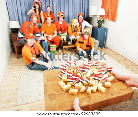 Pre-game snack time. A sports fan carries a cutting board with cheese, decorated with Dutch flag pins to his friends, waiting full anticipation for the game to start. - stock photo