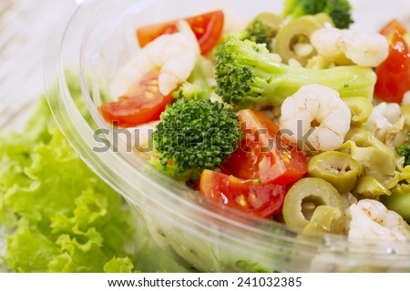 Pre-packed fresh salad,wooden background - stock photo
