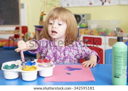 Pre School Child Painting Picture In Classroom - stock photo