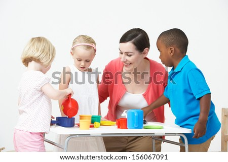 Pre School Children Enjoying Tea Party With Teacher - stock photo