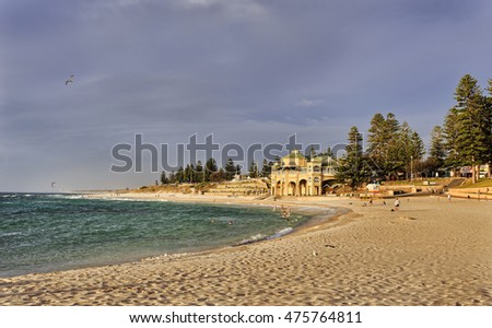 pre-sunset Cottlesloe beach in Western Australia Perth on Indian ocean coast. Relaxing people enjoying water recreational activities on a clean sand and blue water around beach pavilion.