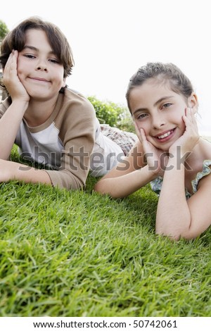 Pre-teen boy and girl reclining, hands on chin on grass - stock photo
