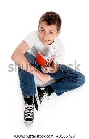 Pre teen boy sits casually on the floor with a book.  He is wearing jeans, t-shirt and sneakers and looking up at camera and smiling cheerfully.  Shadow under boy. - stock photo