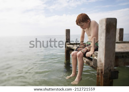 Pre-teen boy sitting on end of pier with feet in water portrait - stock photo