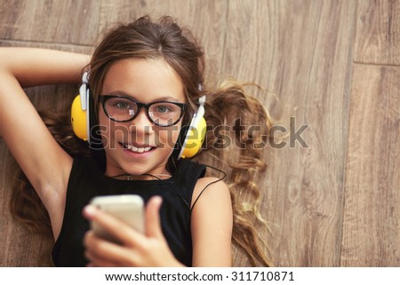 Pre teen child is relaxing on the floor in the living room and listening to music, top view point - stock photo