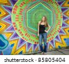 pre-teen girl in front of mural - stock photo