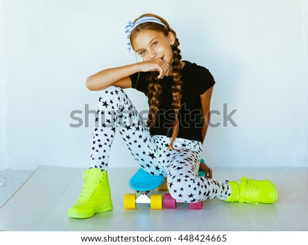 Pre teen girl wearing cool fashion clothing and sneakers posing with colorful skateboard against white wall - stock photo