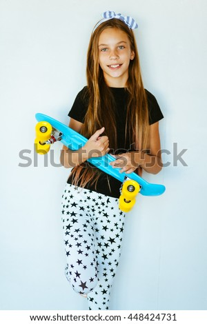 Pre teen girl wearing cool fashion clothing posing with colorful skateboard against white wall - stock photo