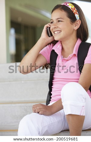 Pre teen girl with phone at school - stock photo
