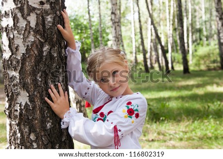 Pre-teenage girl in Ukrainian | Russian style shirt by a birch in a forest