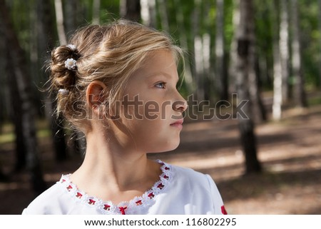 Pre-teenage girl  posing in a birch forest