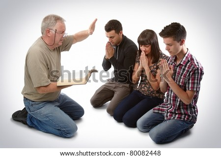 Preacher leading three young souls in prayer to receive Jesus - stock photo