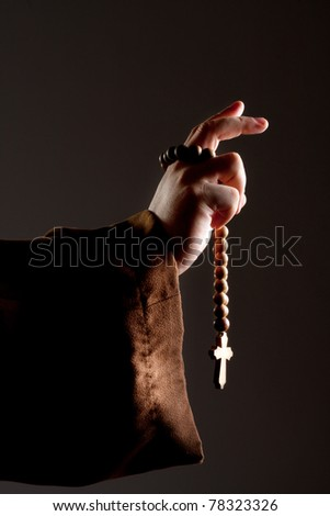 Preaching medieval monk hand with wooden rosary - stock photo
