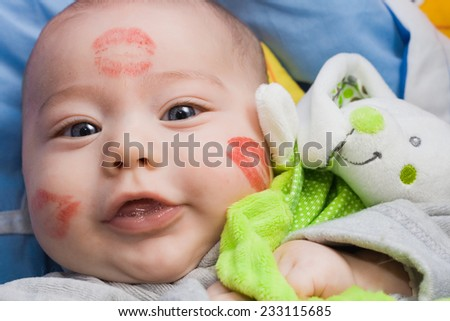 Precious baby has a lot of lip prints red - stock photo