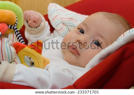 precious baby sitting in a red hammock - stock photo