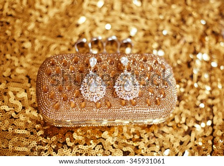 Precious Gem fashion earring with diamonds gems with Shiny Crystal purse on sequins sparkling sequined textile. Women accessories. - stock photo