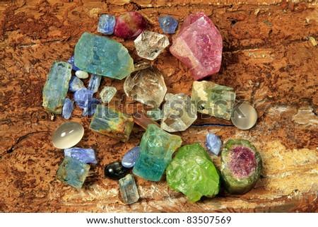 Precious stones like, aquamarine, tourmaline, peridot, and saphire on a wooden backgrond - stock photo