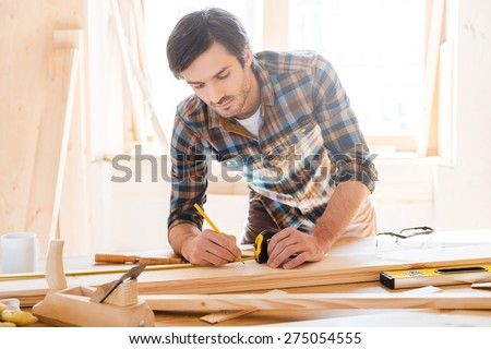 Precision throughout. Serious young male carpenter working with wood in his workshop - stock photo