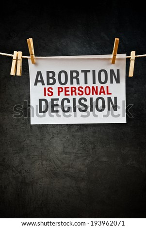 Pregnancy Abortion is personal decision, message printed on paper hanged on rope with clothes pins. - stock photo